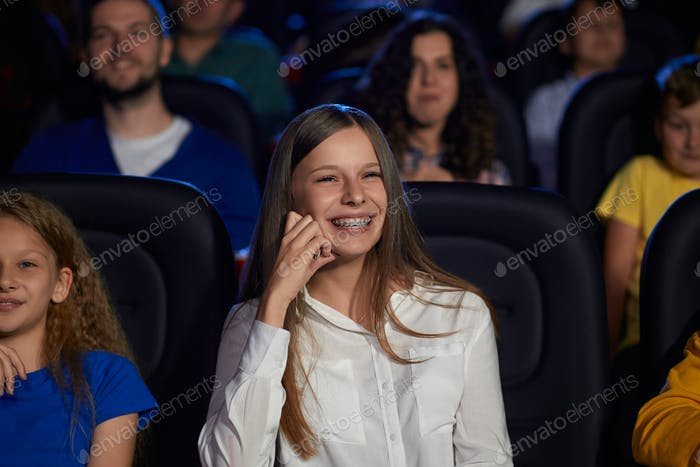 Young laughing girl with dental braces in cinema