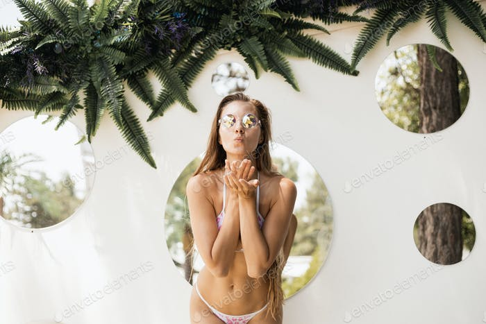 Slim beautiful girl in a swimsuits and sunglasses is posing against the wall with round mirrors on