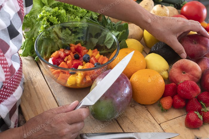 A wooden cutboard  full of fruits and vegetables. A woman prepare a vegetarian fruit salad