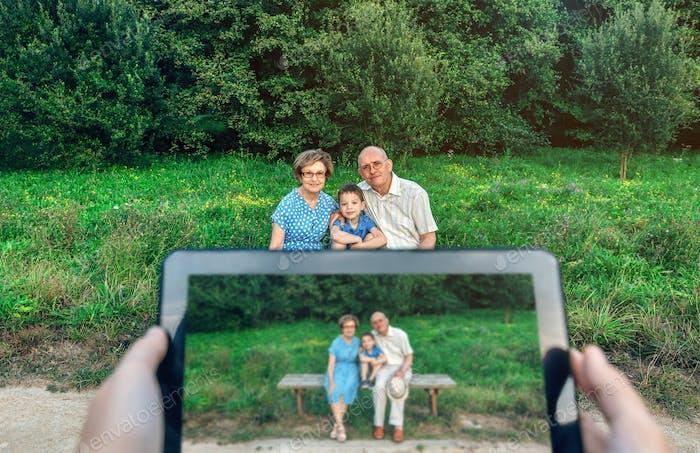 Großeltern und Enkel posieren für ein Bild mit Tablet