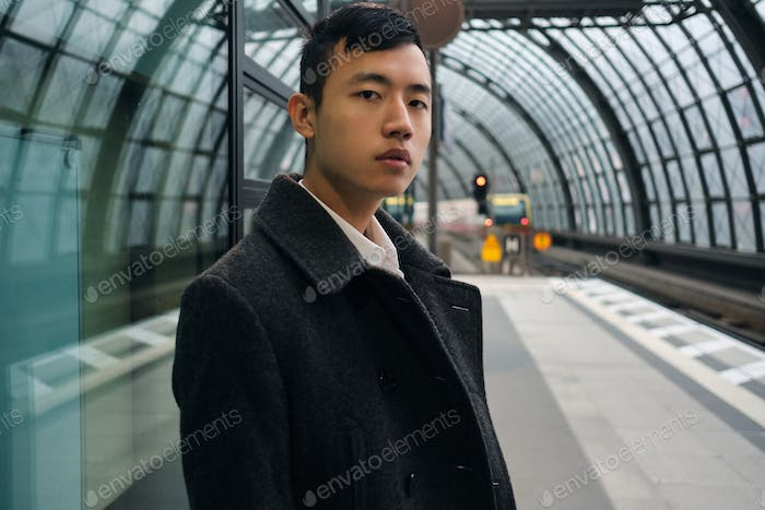 Portrait of young Asian businessman intently looking in camera at city subway station