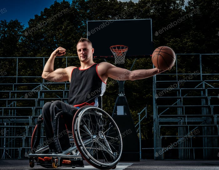 Strong basketball player in wheelchair pose with a ball on open gaming ground.