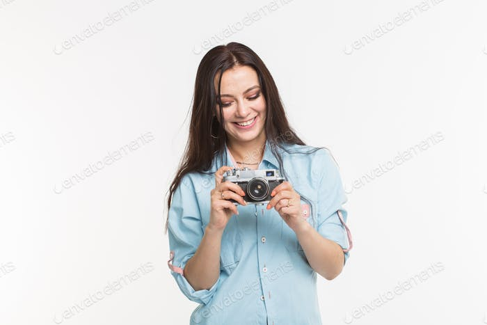 Happy european female model with dark hair enjoying indoor photoshoot. Young woman is looking at her
