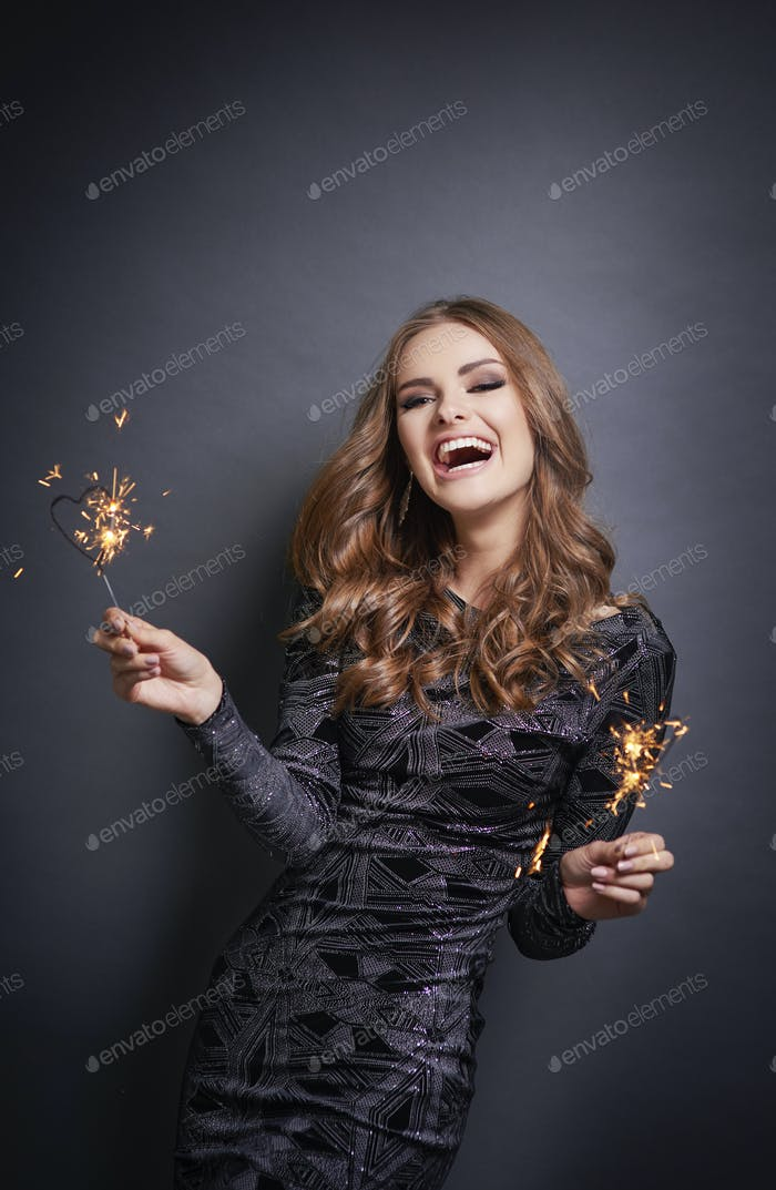 Cheerful woman with sparkler laughing in studio shot