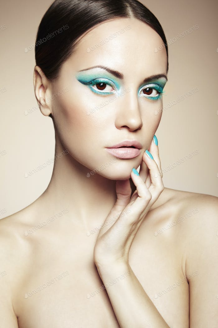 Beautiful young woman with bright make-up and manicure