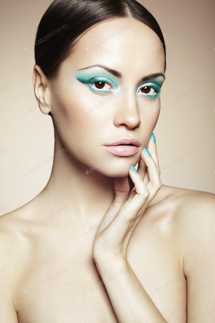 Schöne junge Frau mit hellen Make-up und Maniküre