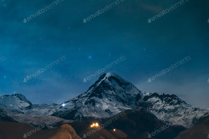 Stepantsminda, Georgia. Natural Night Starry Sky With Glowing St