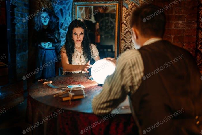 Paar auf spirituelle Seance, Hexe auf Hintergrund