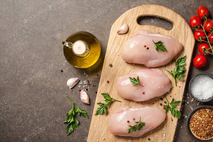 Fresh raw chicken fillets with ingredients for cooking