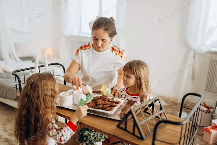 Young beautiful mother and her two charming little daughters sit