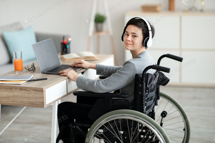 Impaired teenager in wheelchair studying online with laptop, using headphones for remote