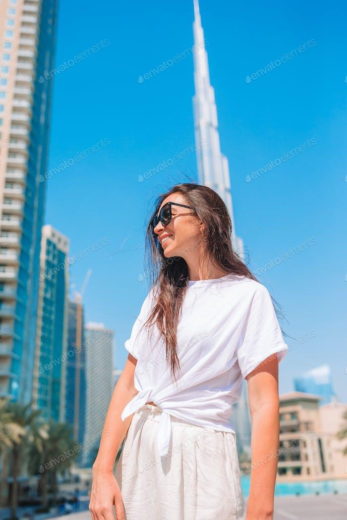 Happy woman walking in Dubai with Burj Khalifa skyscraper in the background