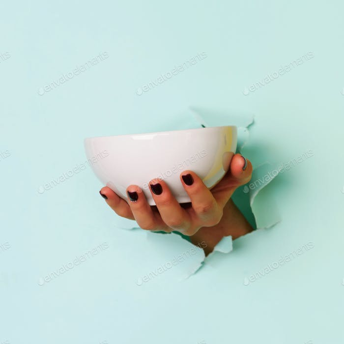Female hand holding empty bowl on blue background with copy space. Healthy eating, dieting concept