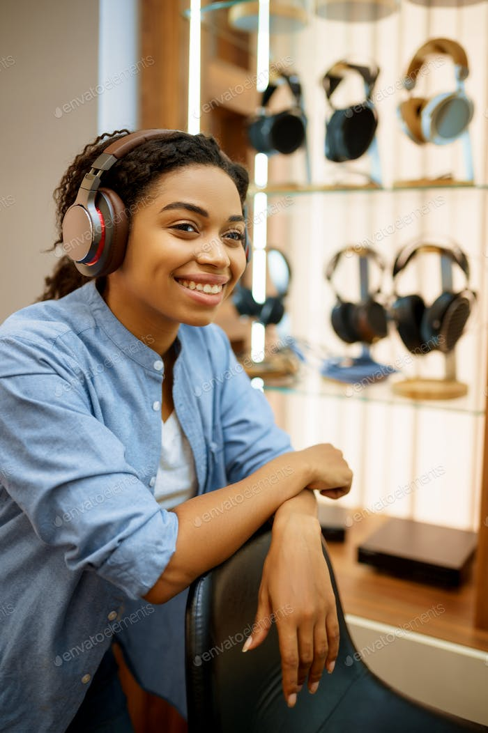 Young woman listening to music, headphones store