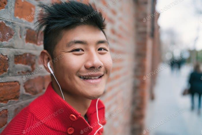 Asiatische Junge hören Musik mit Ohrhörern.