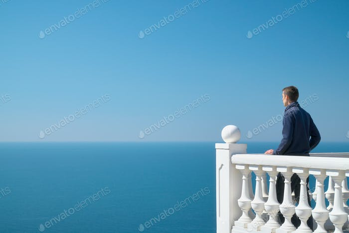 Man standing on balcony and look on the sea