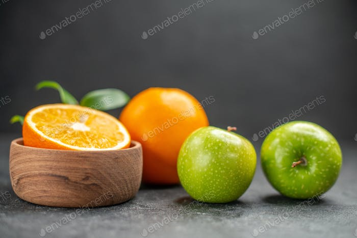Side view of benefit fruit salad with fresh oranges and green apple on dark background