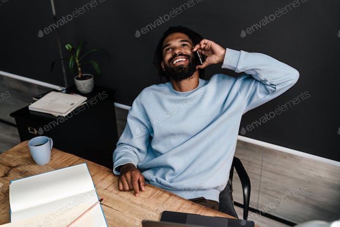 Умный молодой африканский человек сидит за столом