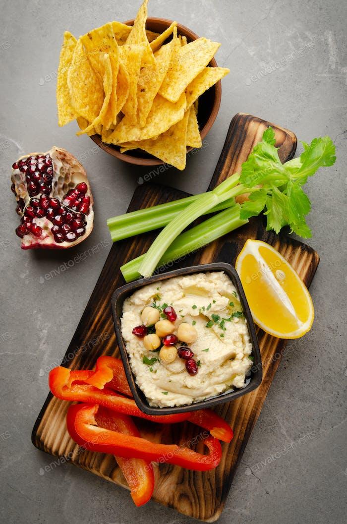Flacher Blick auf Gemüse-Hummus-Dip-Teller mit Kichererbsen