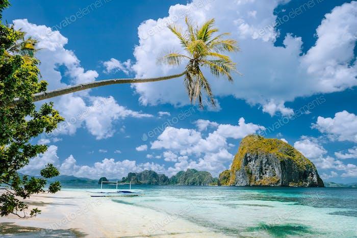 El Nido, Palawan, Philippinen. Tropische Landschaft von exotischen Strand mit Palme, Boot auf dem Sand