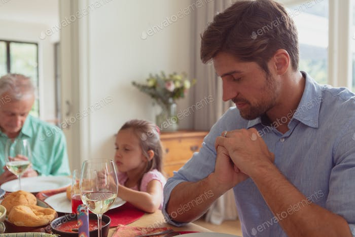 Side view of multi-generation Caucasian family praying before having food on dining table at home