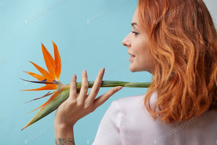 Exotic flower strelitzia decorates shoulder smiling woman on a blue background with copy space
