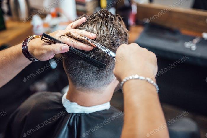 мастер в парикмахерской бриет и режет мужчину