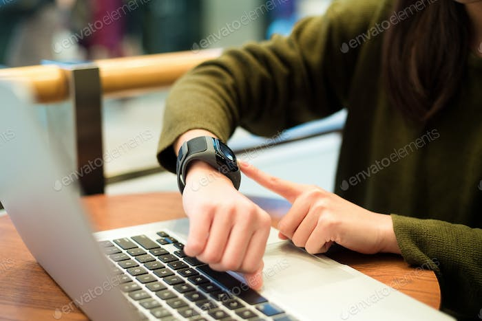 Woman connecting smart watch on laptop computer