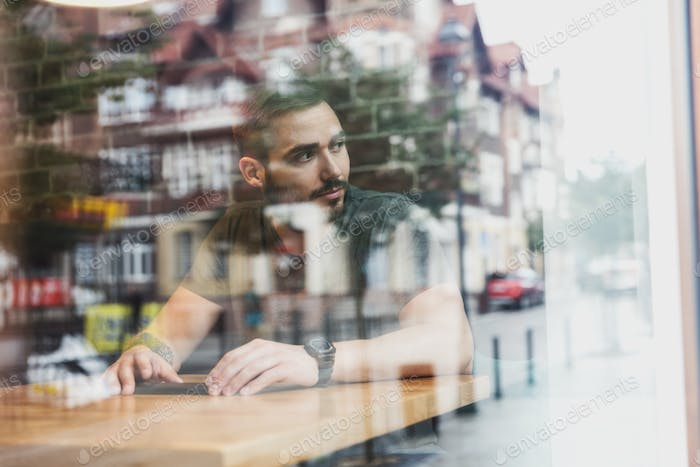 Man in a cafe reflecting in glass. City life