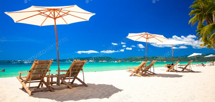 Beach chairs and umbrellas on exotic tropical white sandy beach