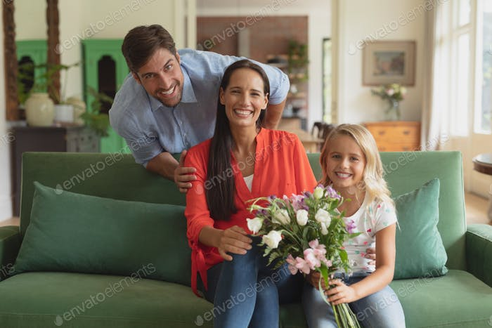 Portrait of Caucasian family with flower bouquet sitting on sofa in living room at home