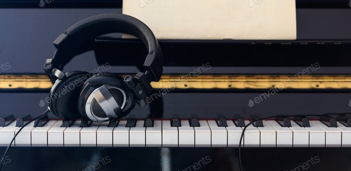 Headphones on piano keyboard, front view