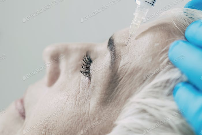 Anti-Aging Injections. Senior Woman Receiving Botulinum Toxin In