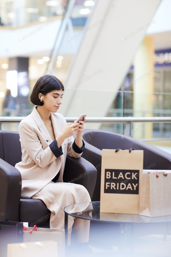 Woman using Smartphone While Relaxing in Shopping Mall