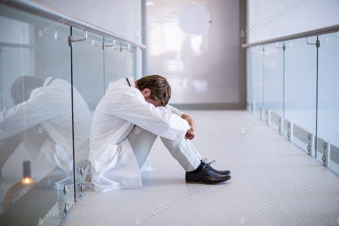 Tensed doctor sitting in corridor