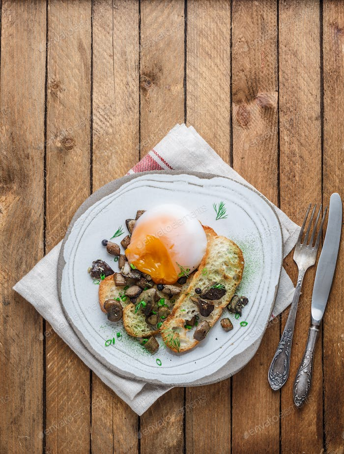 Poached egg with bread and wild mushrooms, copy space