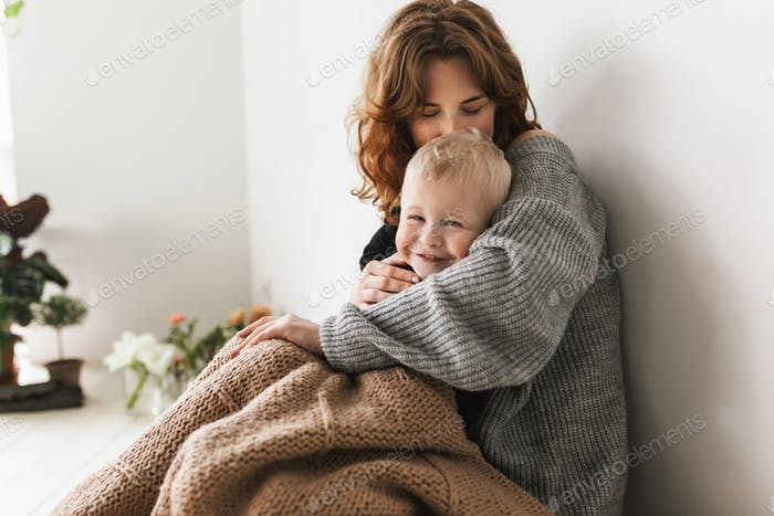 Young beautiful mom with red hair in knitted sweater sitting on floor kissing her little son