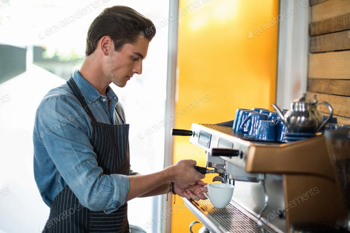 Waiter making cup of coffee at counter