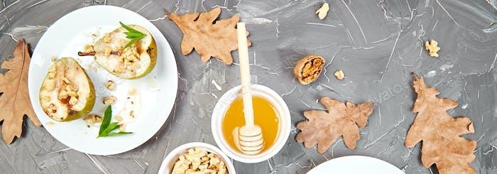 Banner mit schmackhaften Braten Birnen mit Honig und Walnüssen auf grauem Hintergrund Tisch.