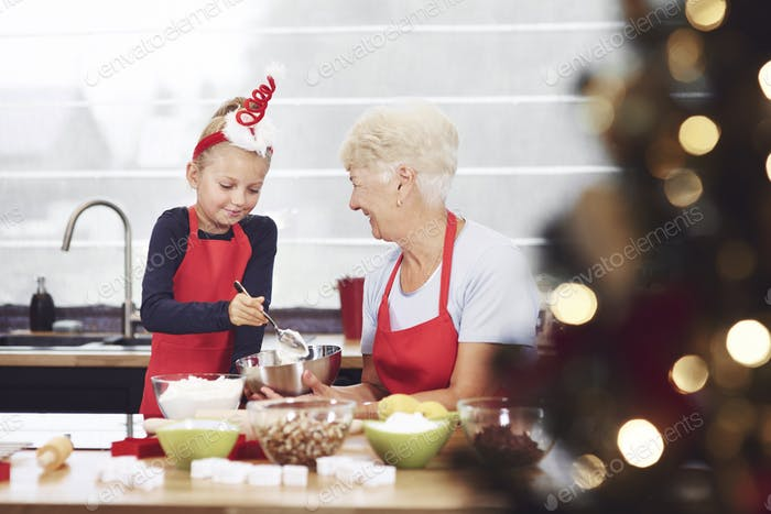 Grandmother supervising her granddaughter while cooking