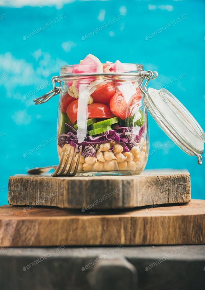Vegetable and chickpea sprout vegan salad jar, blue wall background