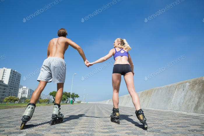 Fit couple rollerblading together on the promenade on a sunny day