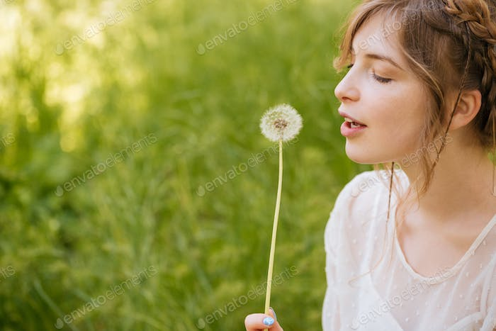 Lovely woman holding and blowing on dandelion outdoors