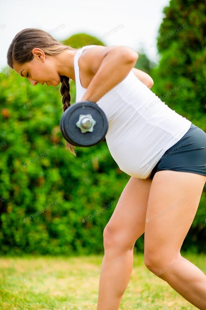 Fit Schwangere Frau Trainieren mit Hanteln im Park