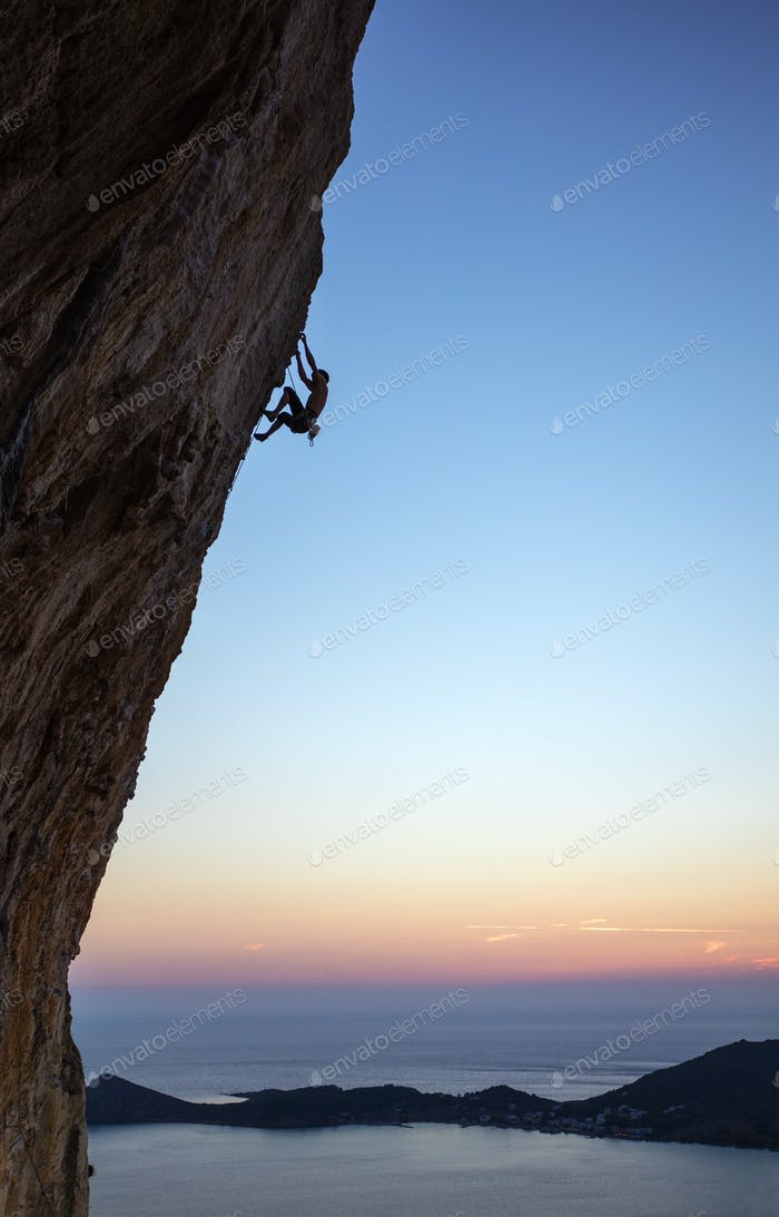 Rock climber on overhanging cliff at sunset. Kalymnos Island, Greece