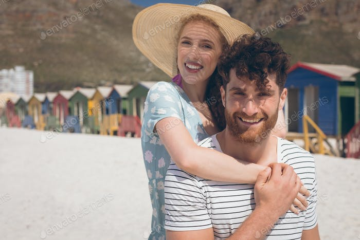 Romantic Caucasian couple smiling and looking at camera standing at beach on a sunny day.