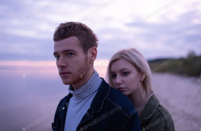 Young couple on lake shore in evening