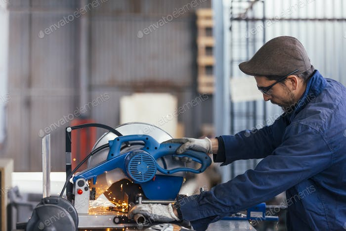 Side view of bearded master working with saw machine