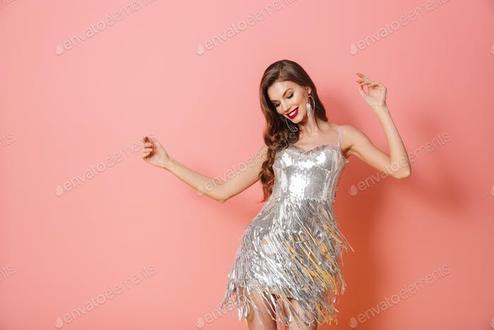 Smiling young woman in bright sequins dress