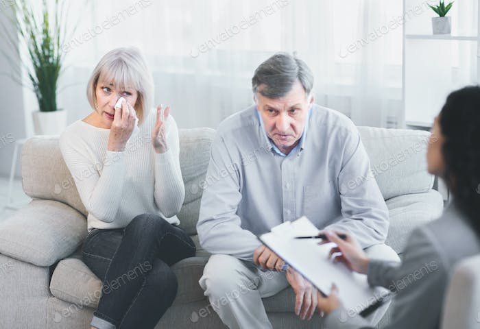 Sad husband and wife talking to psychotherapist